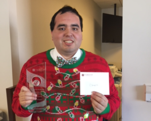 Enrique in a holiday sweater holding his Culture Champion award