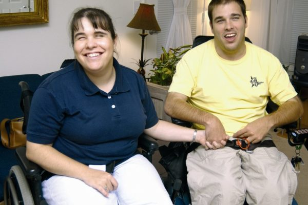 A woman and man in wheelchairs smiling.