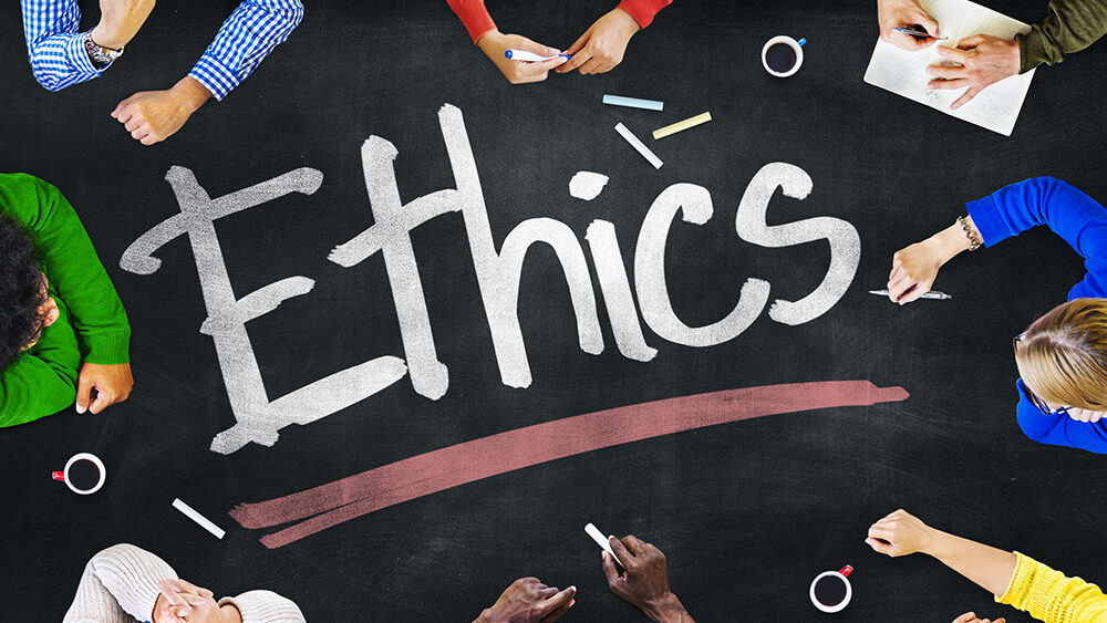 """A group of people sitting around a chalkboard table with the word """"ethics"""" written in the middle"""